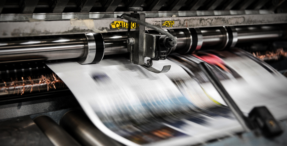 Image showing a printing press with paper flying by very quickly, representing the speed and efficiency that Conquest Graphics has worked to improve continually through print automation.
